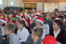Children sing as they leave the last assembly of term